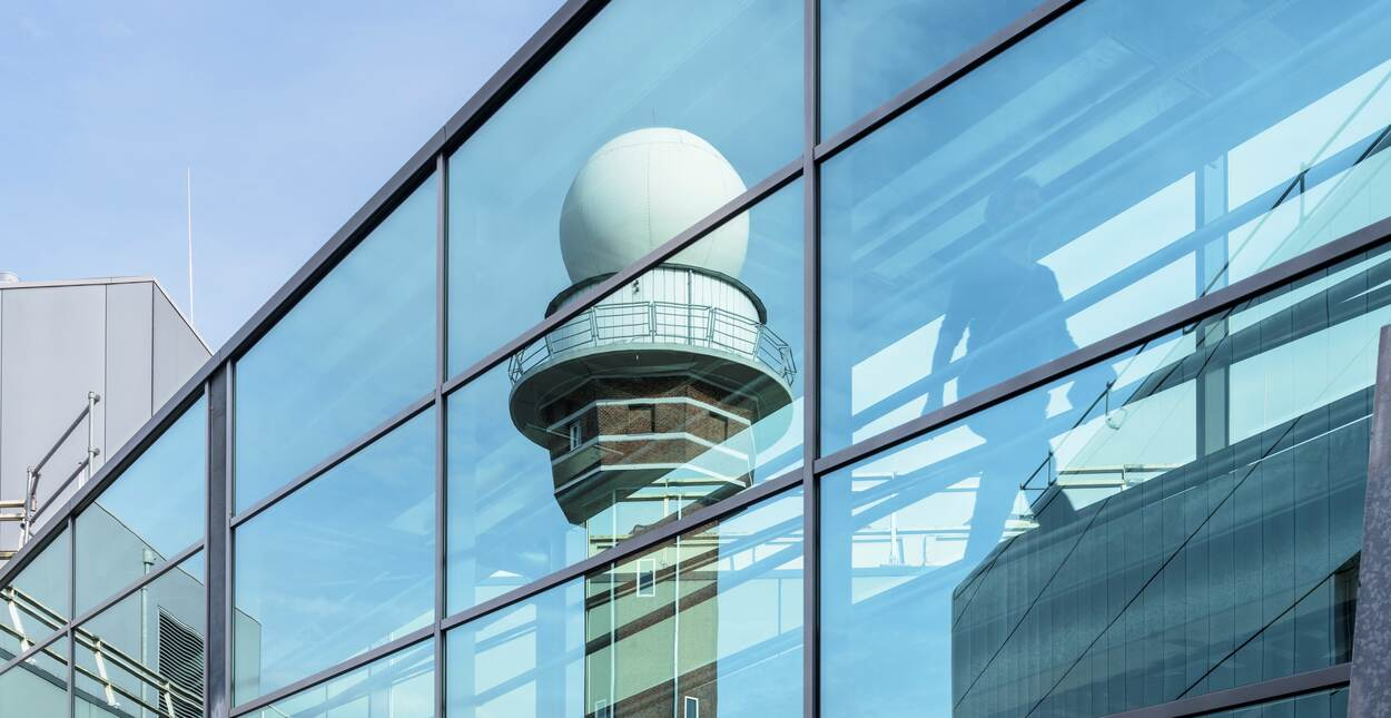Radar tower reflects in the glass KNMI building